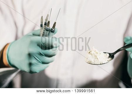 Close-up of a person holding a spoon with cocaine and several syringes