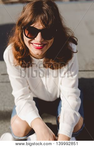 Close shot of young pretty woman with sunglasses red lips and white shirt