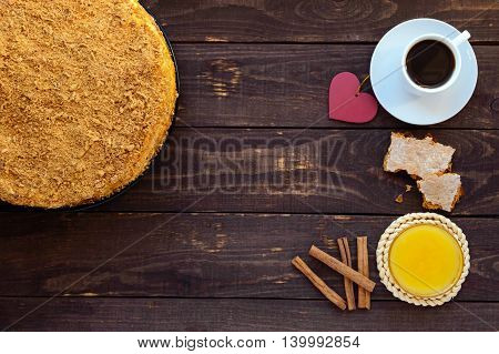 Honey cake and cup of coffee on a dark wooden background. The top view.