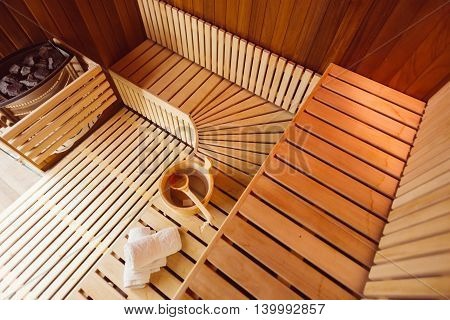 Interior of a wooden sauna roomwith towelsbucket and ladle view from the top