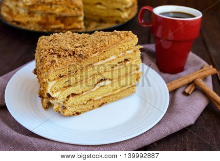 Honey cake and cup of coffee on a dark wooden background. Cutting a piece. The top view.