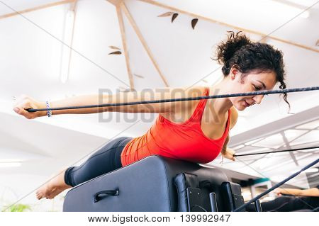 Young woman stretching on a reformer bed