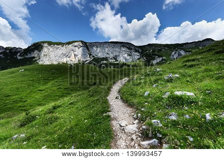 Low angle view of mountain range with hiking path under cloudy sky. Achensee Area Tyrol Austria.