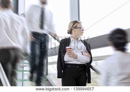 Busy office building corridor three business people in a motion focus on woman standing and holding a cup of coffee