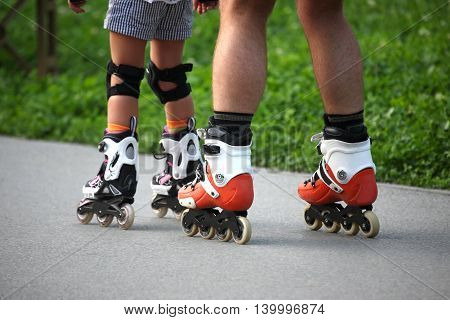 two pairs of legs on roller skates