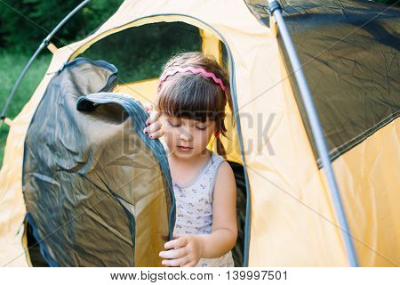 Little girl getting out of tent in forest. Young girl studying camping lifestyle.