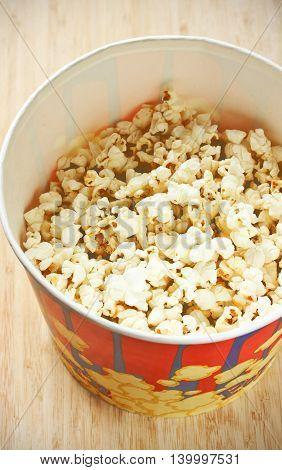Popcorn in big paper bucket top view selective focus