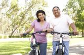 picture of portrait middle-aged man  - Senior Couple Riding Bikes In Park - JPG