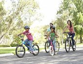 picture of family fun  - Young Family Riding Bikes In Park - JPG