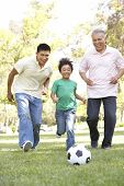 stock photo of grown up  - Grandfather With Son And Grandson Playing Football In Park - JPG