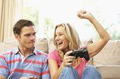 Постер, плакат: Молодая пара Игры компьютерные игры на диване у себя дома