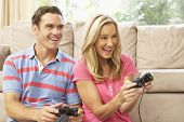stock photo of video game controller  - Young Couple Playing Computer Game On Sofa At Home - JPG