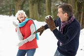 stock photo of snowball-fight  - Senior Couple Having Snowball Fight In Snowy Woodland - JPG