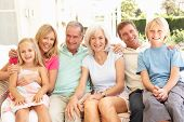 stock photo of extend  - Extended Family Relaxing Together On Sofa - JPG