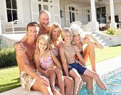 stock photo of extend  - Extended Family Outside Relaxing By Swimming Pool - JPG