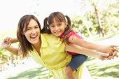 stock photo of piggyback ride  - Mother Giving Daughter Ride On Back In Park - JPG