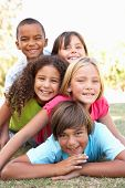 stock photo of children playing  - Group Of Children Piled Up In Park - JPG