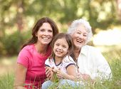 stock photo of grown up  - Grandmother With Daughter And Granddaughter In Park - JPG