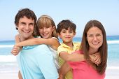 stock photo of family fun  - Family Having Piggyback Fun On Beach Holiday - JPG