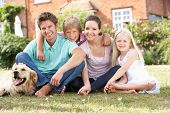 stock photo of dog-house  - Family Sitting In Garden Together - JPG