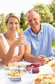 stock photo of woman couple  - Couple Enjoying Meal In Garden - JPG