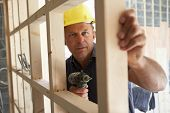 picture of framing a building  - Construction Worker Building Timber Frame In New Home - JPG