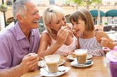 stock photo of old couple  - Grandparents With Granddaughter Enjoying Coffee And Cake In Cafe - JPG