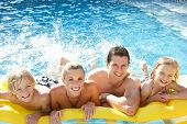stock photo of ten years old  - Young family having fun together in pool - JPG