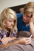 stock photo of teen pregnancy  - Two Teenage Girls Lying On Bed Looking At Pregnancy Testing Kit - JPG