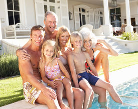stock photo of swimming pool family  - Extended Family Outside Relaxing By Swimming Pool - JPG