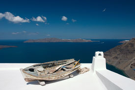 foto of greek-island  - Old damaged rowing boat placed on house roof - JPG
