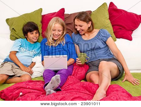 mother sitting on a sofa with her children, they are learning on the computer