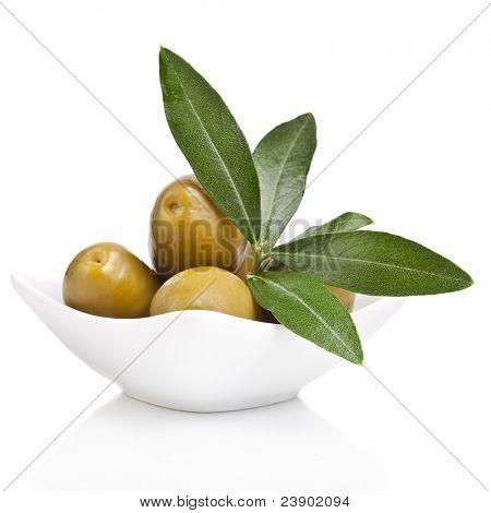 eingelegte grüne Oliven in eine Schüssel und Olive Ast auf weißem Hintergrund