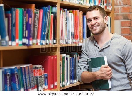 Smiling male student holding a book in a library