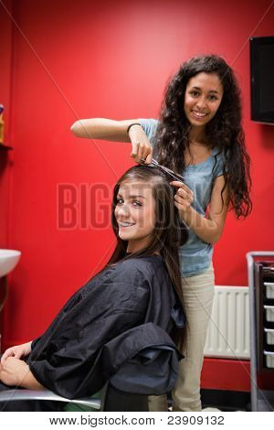 Portrait of a happy hairdresser cutting hair while looking at the camera