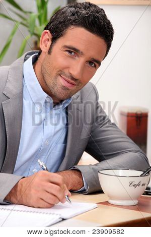 charming 30 years old man dressed in a grey suit and writing in a cosy place