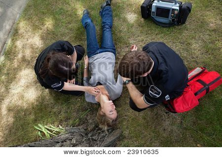 Emergency medical team responding to a woman in a park