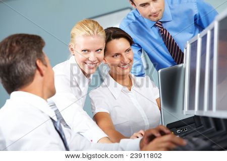 Group of four business people watching computer presentation together and discussing it