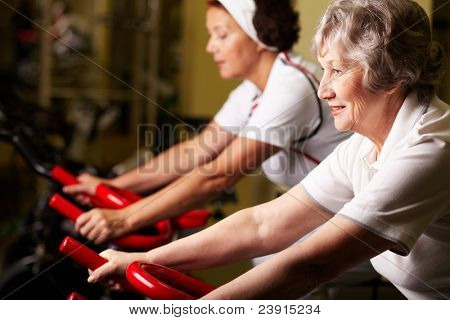 Two senior women training in gym