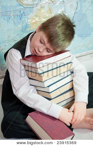 Tired Schoolboy With A Pile Of Books On A Map Of The World