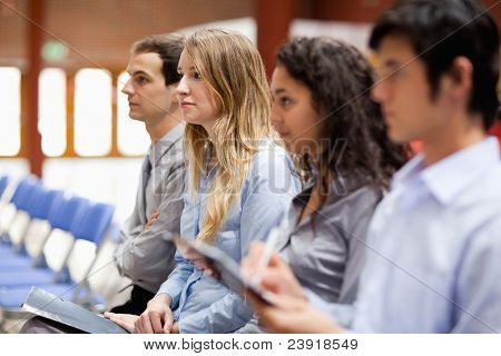Business people listening and taking notes during a presentation