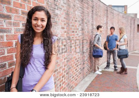 Smiling student posing while her friends are talking outside building