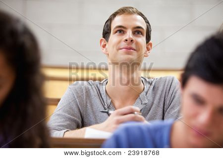 Smiling student listening to a lecturer in a amphitheater