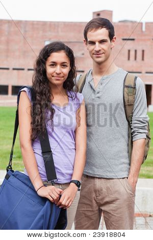 Portrait of a student couple posing outside a building