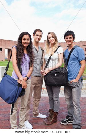 Portrait of fellow students posing outside a building