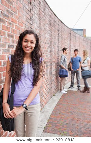Portrait of a smiling student posing while her friends are talking outside a building