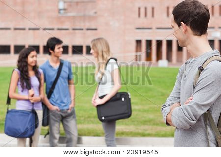 Student looking at his classmates talking outside a building