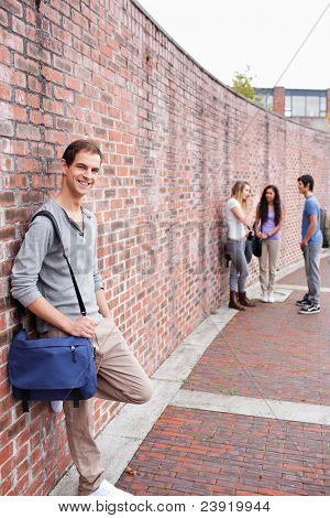 Portrait of a male student leaning on a wall while his friends are talking outside a building