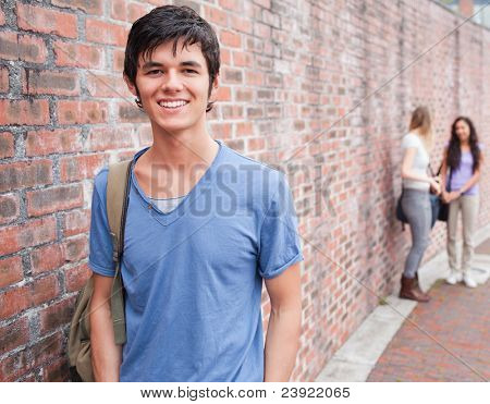 Handsome student posing while his friends are talking outside a building