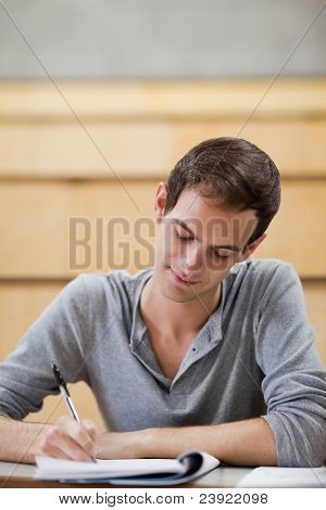 Portrait of a male student writing on a notepad in an amphitheater